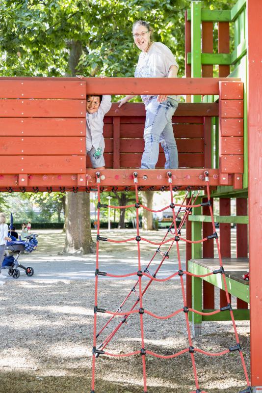 Une femme et son enfant jouent sur place de jeux.
