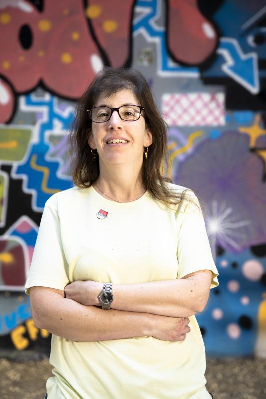 Eine Frau mit Brille und verschränkten Armen vor einer bemalten Wand.