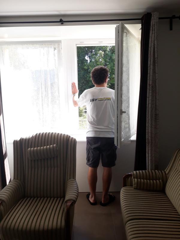 Un homme se tient de dos et regarde par la fenêtre.