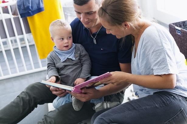 Des parents lisent une histoire à leur enfant.