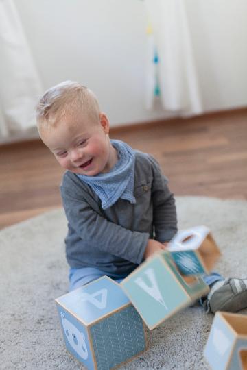 Un enfant rigole en jouant avec des cubes en bois.