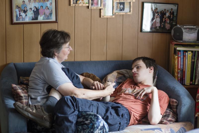 Une femme est assise sur le canapé et tient la main de son fils couché.