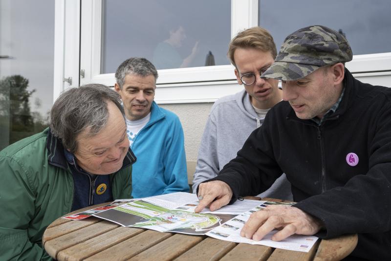 Vier Männer sitzen an einem runden Tisch und studieren eine Broschüre.