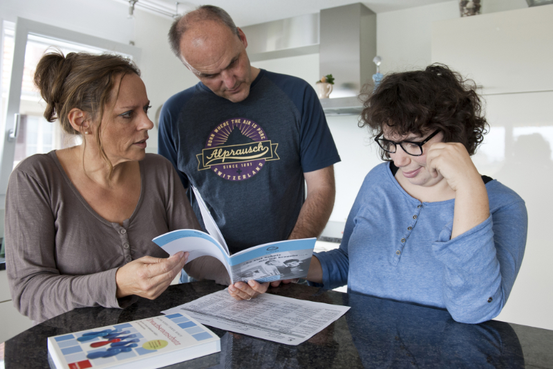 Eine Frau und ein Mann schauen mit ihrer Tochter eine Broschüre an.