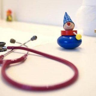 Un stéthoscope posé sur une table à côté d'un jouet en bois
