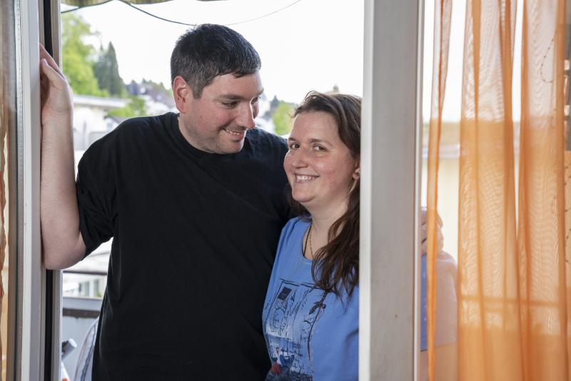 Un homme enlace sa femme et la regarde avec affection.