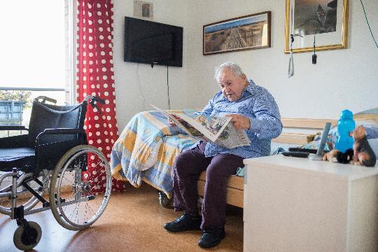 Un homme âgé est assis sur son lit et lit le journal.
