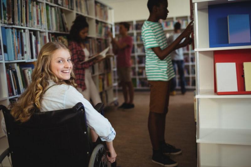 Eine junge Frau sitzt in einer Bibliothek im Rollstuhl und blickt über ihre Schulter.