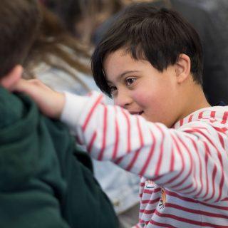 Ein Junge im rot-weiss gestreiften Pullover legt einem anderen Jungen die Hand auf die Schulter.