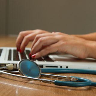 Une femme est en train d'écrire sur son ordinateur portable.