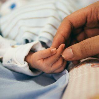 Une mère tient dans sa main celle de son bébé.