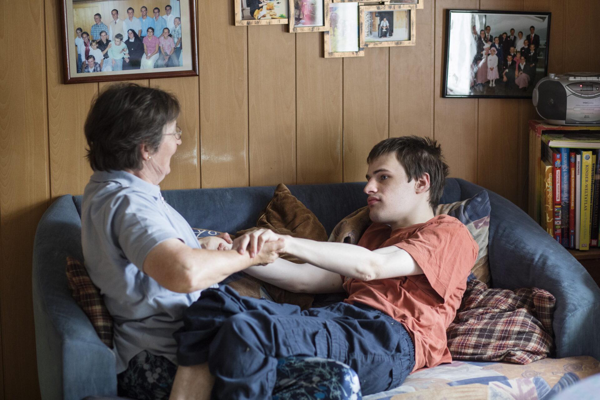 Une mère aide son fils allongé sur un canapé.