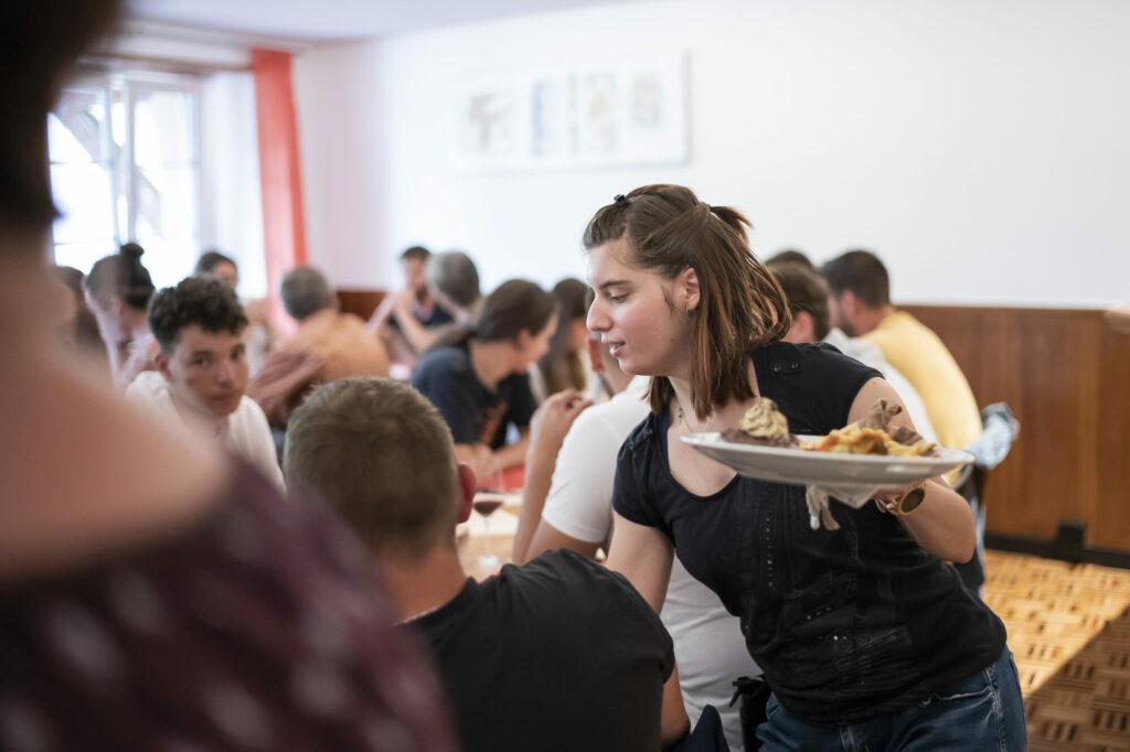 Une jeune femme fait le service dans un restaurant.
